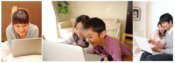 パソコンを笑顔で使う人々の写真